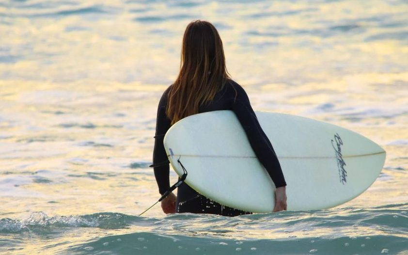 woman waist deep in ocean holding surfboard