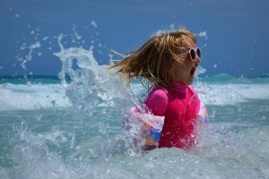 young girl making a surprised face as wave hits her
