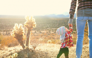 mom in desert holding childs hand