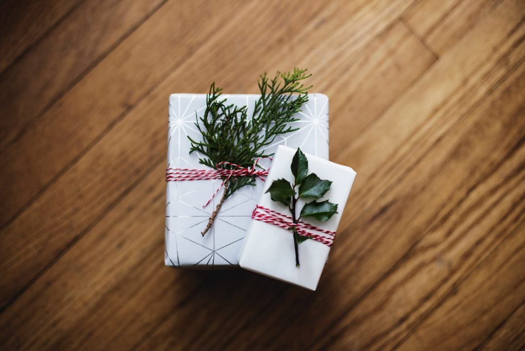 simply wrapped presents with a sprig of greenery in ribbon