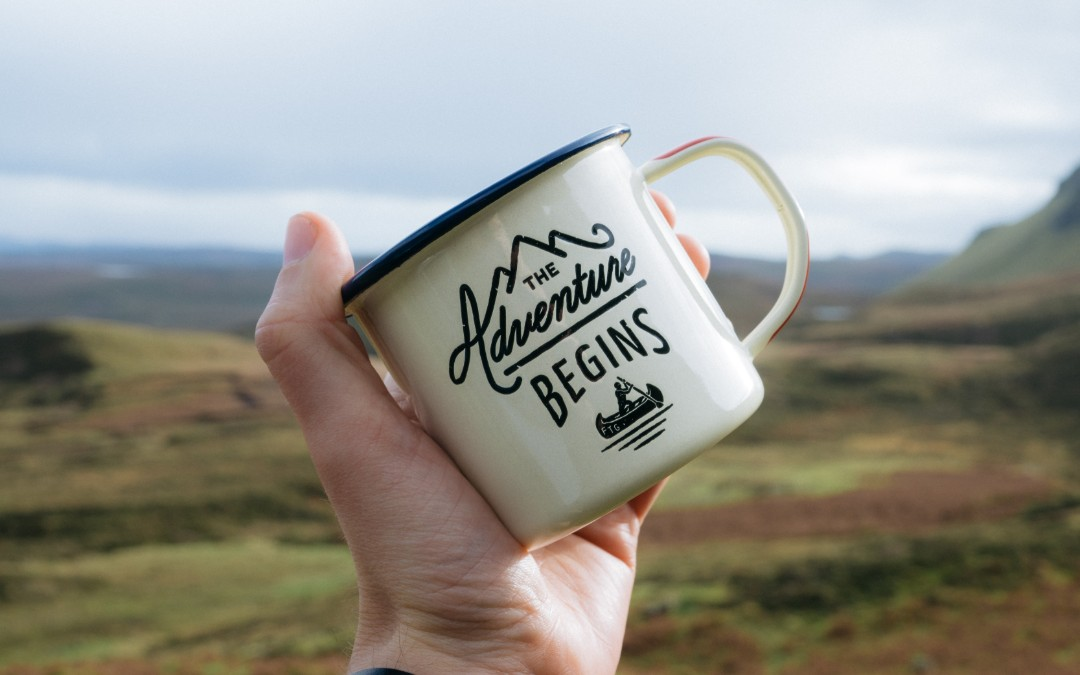 The ultimate guide to adventure for moms hand holding camping mug says the adventure begins