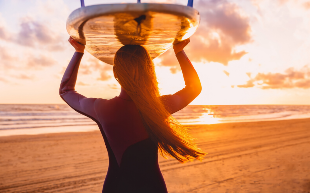 woman holding surfboard on head at sunset