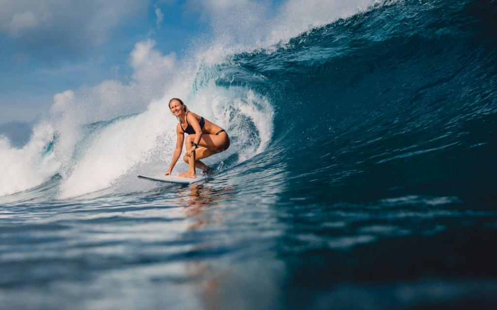 woman in bikini surfing a wave
