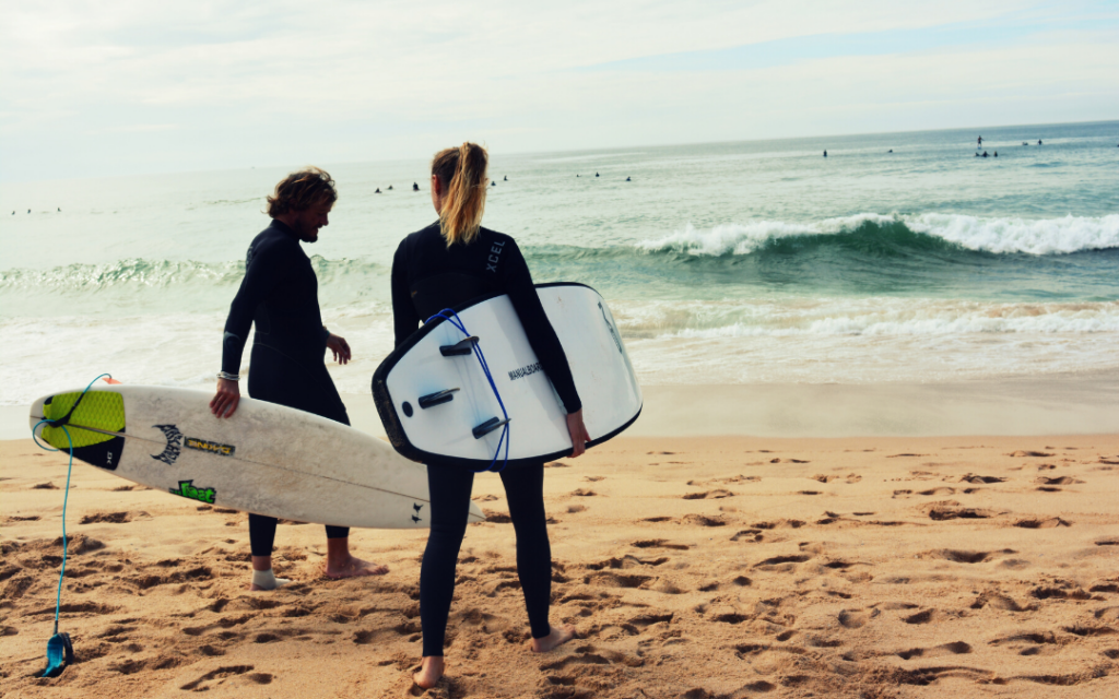 woman and man on beach holding surfboards learning to surf