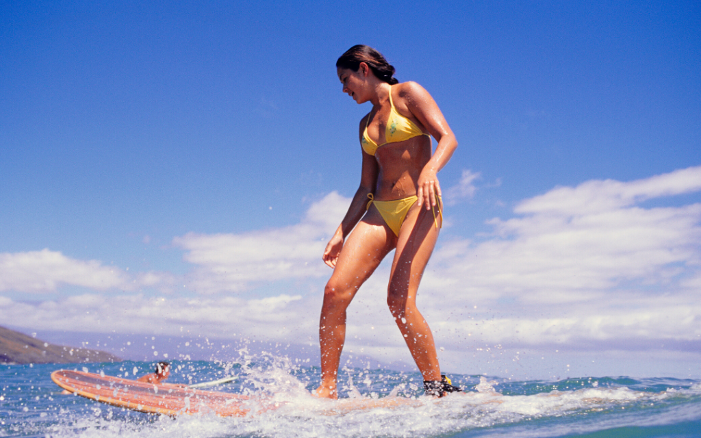 woman in bikini learning to surf a wave